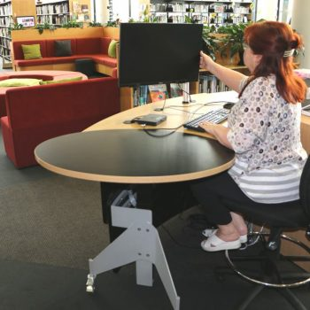 GLO 1600 Desk with its open and invitingform is positioned alongside an area where customers can sit and use devices.